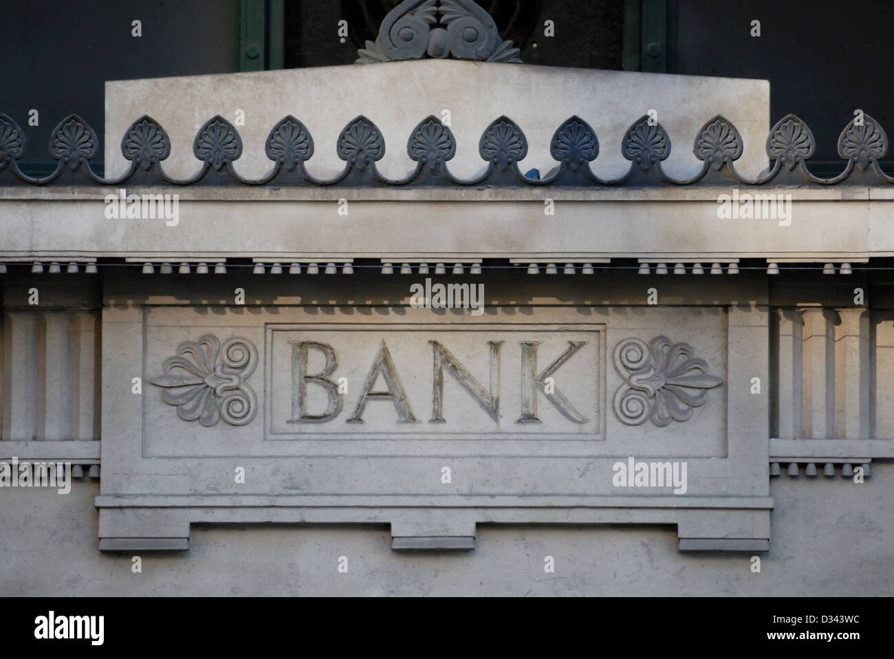 Ornate sign for a bank carved in the masonry above the entrance. The building is no longer used as a bank. - Stock Image