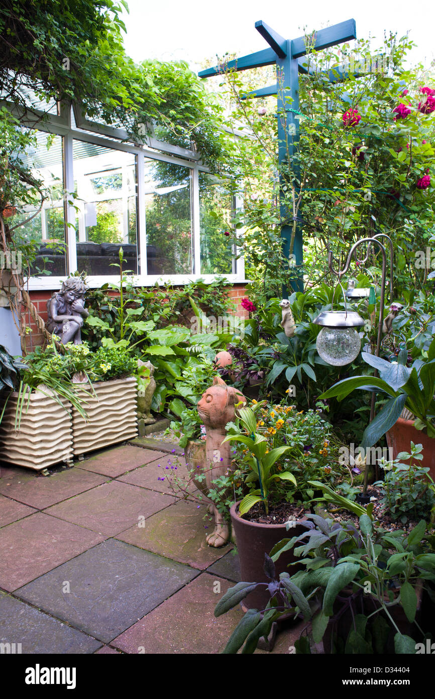 Patio in small town garden full of potted plants and ornaments. Stock Photo