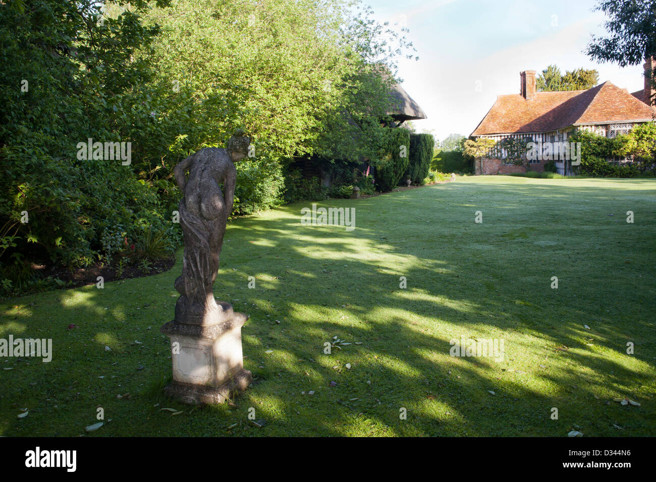 View across the garden towards the house with woman statue in foreground, Bexon Manor. Stock Photo