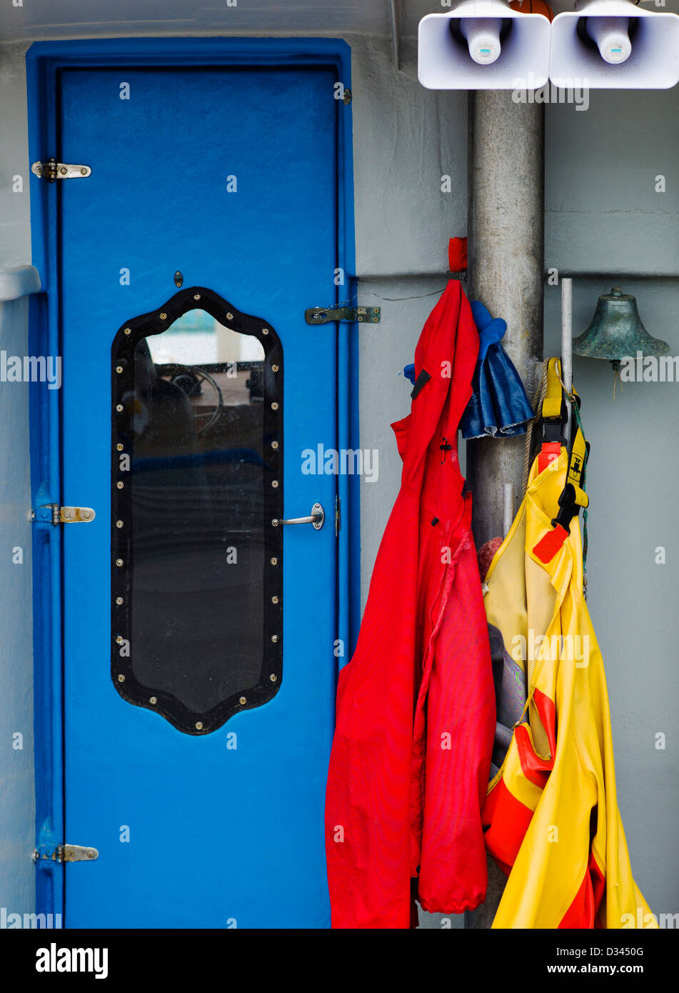 Rain coats and slickers hang on commercial fishing boat in the harbor, Homer, Alaska, USA. Detail of gear and boats. - Stock Image