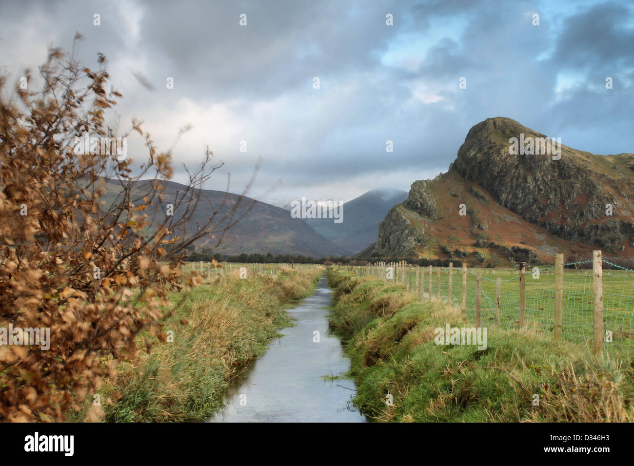 Dyke in fields and Cadir Idris with snow on peak and Craig Yr Aderyn Stock Photo
