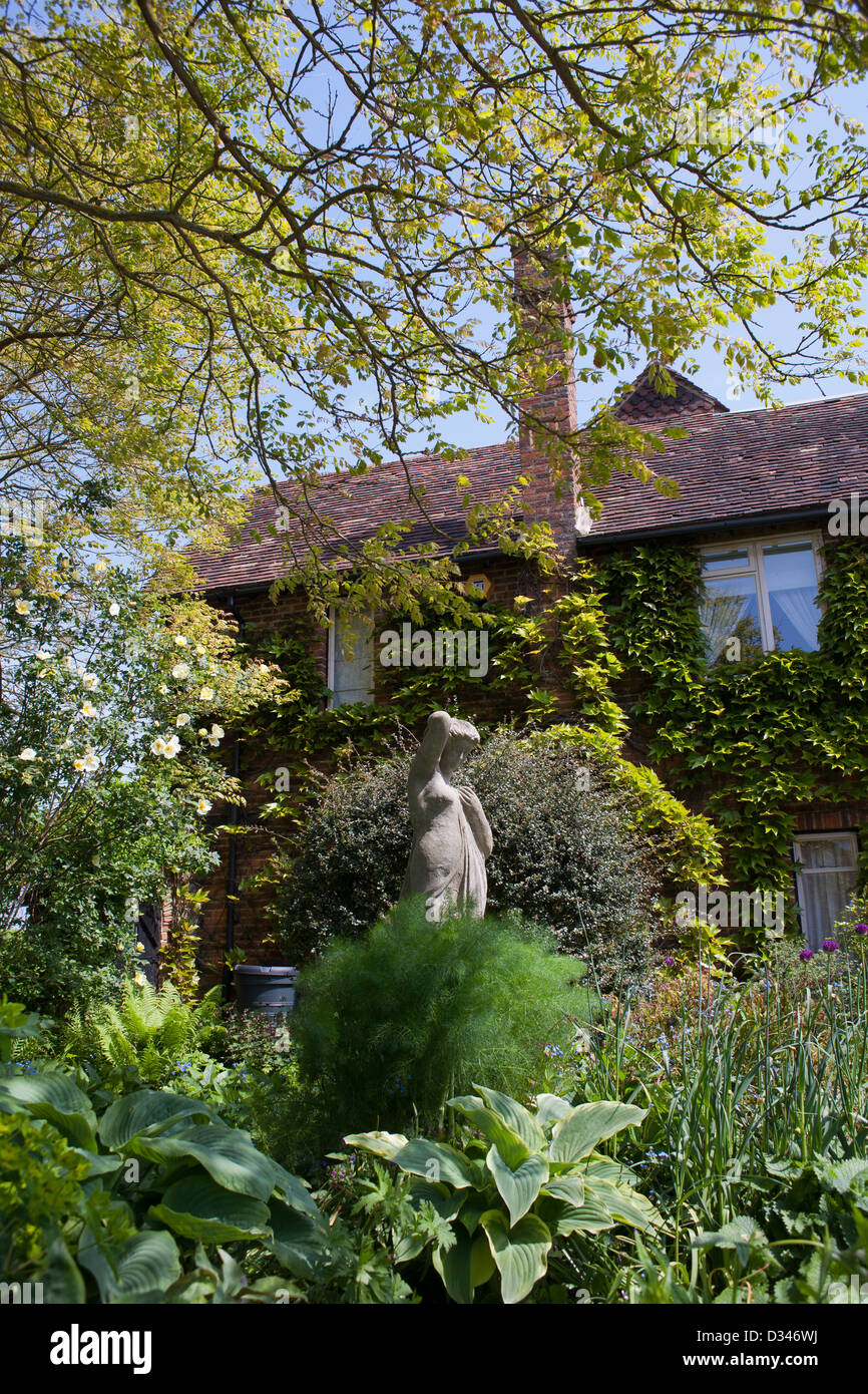 Woman statue in herbaceous borders. House covered with Parthenocissus tricuspidata. Stock Photo