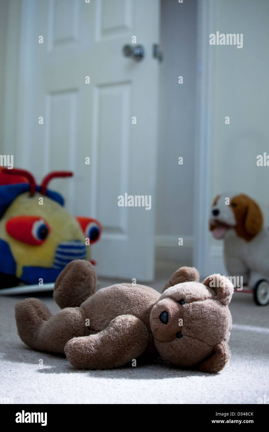 Brown teddy bear laying on a child's bedroom floor. - Stock Image