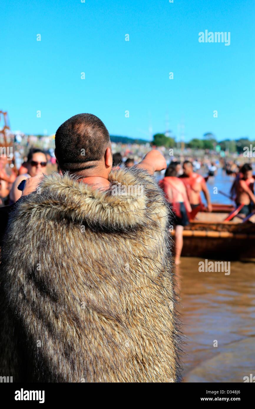 Maori man in traditional feathered cloak on Te Tii beach during Waitangi Day celebrations - Stock Image