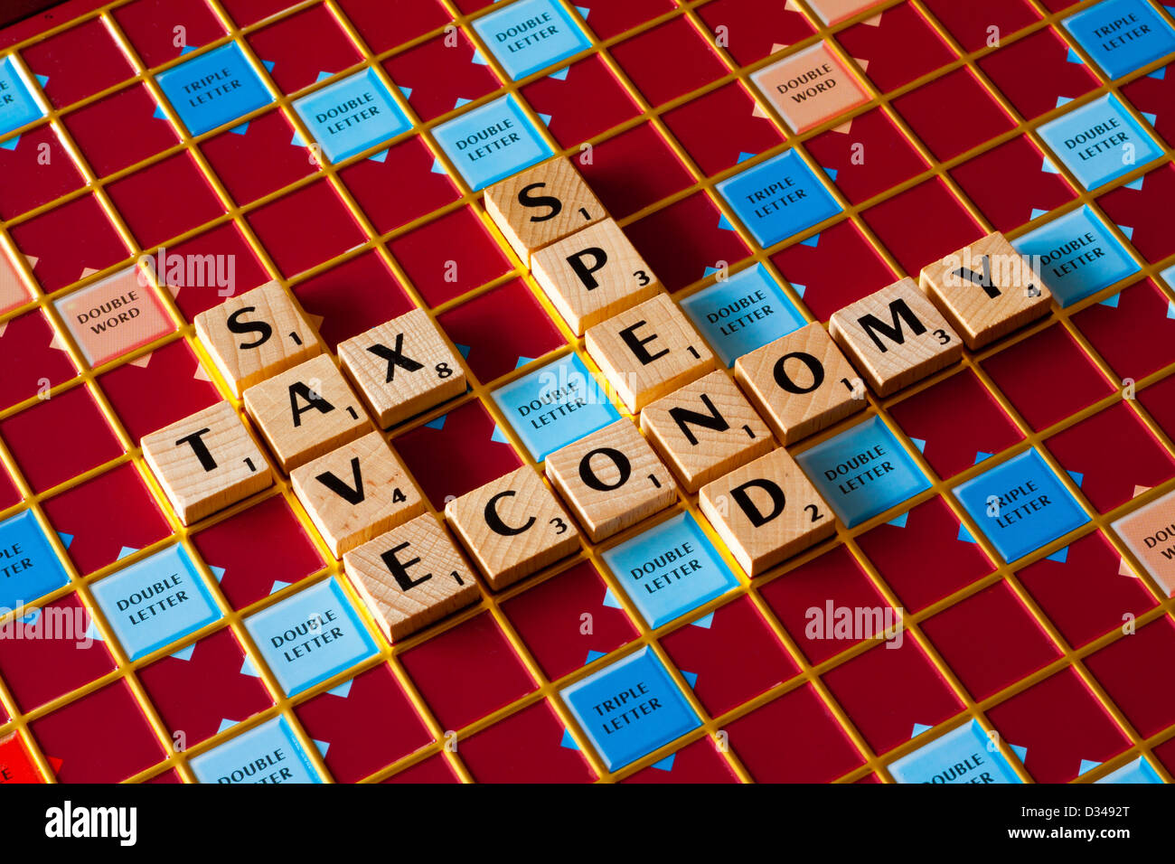 Scrabble board spelling Save Tax Spend Economy words relevant to the budget and state of the economy and finance - Stock Image