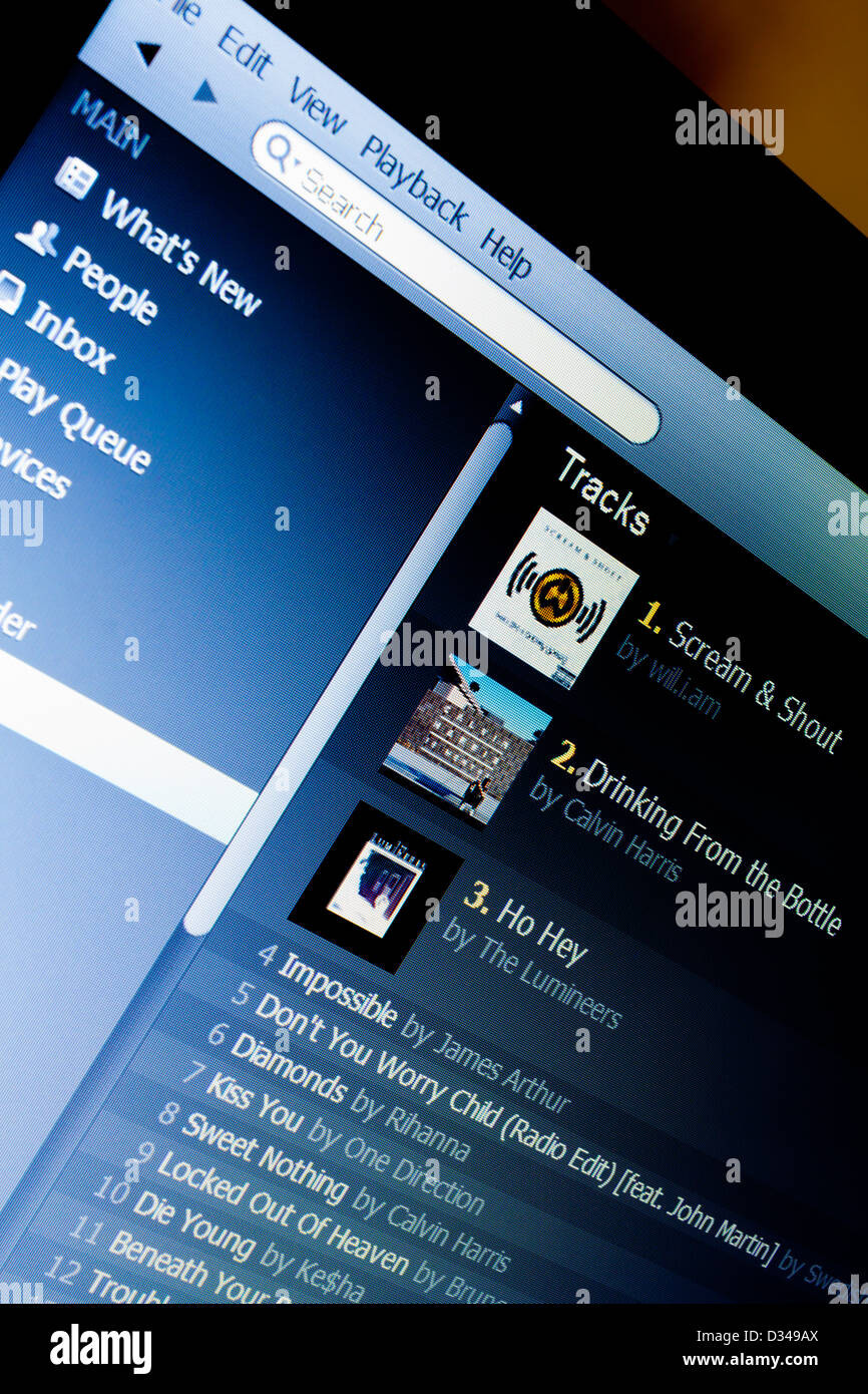 Close up view of Spotify streaming music website with playlists and tracks visible on computer screen - Stock Image