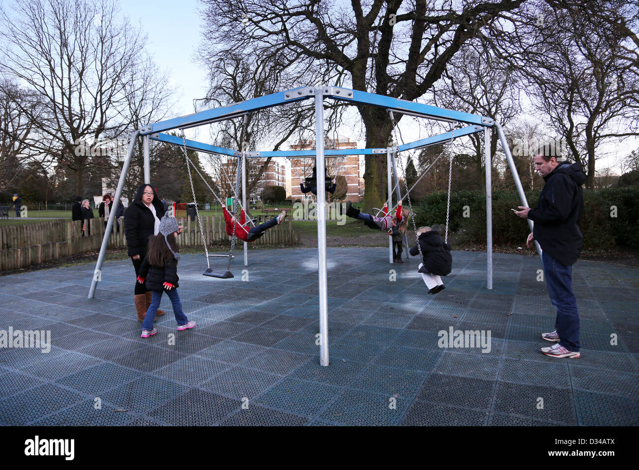 Children On Swings in Playground in the Pleasure Gardens at the Pittville Pump Room Cheltenham Gloucestershire England - Stock Image