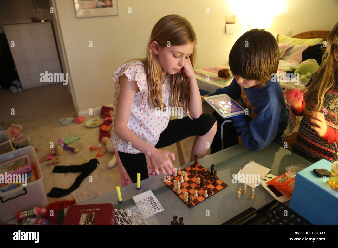 Children Playing Chess In Their Bedroom Boy With IPad Mini England   Stock  Image