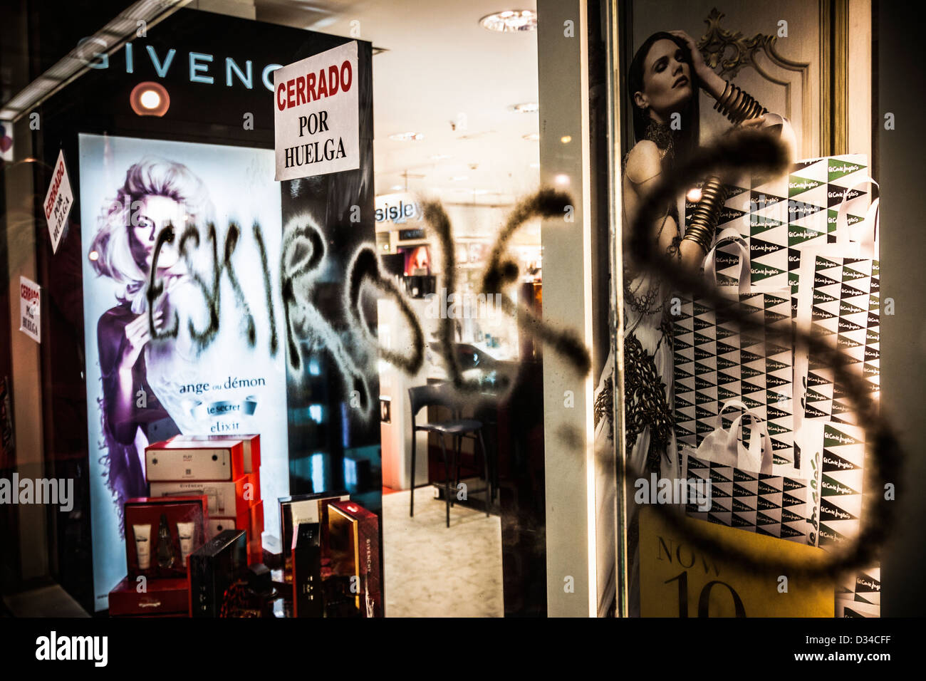 Graffiti reading 'Esquiroles' (blacklegs) on the window of open big department store during general strike - Stock Image