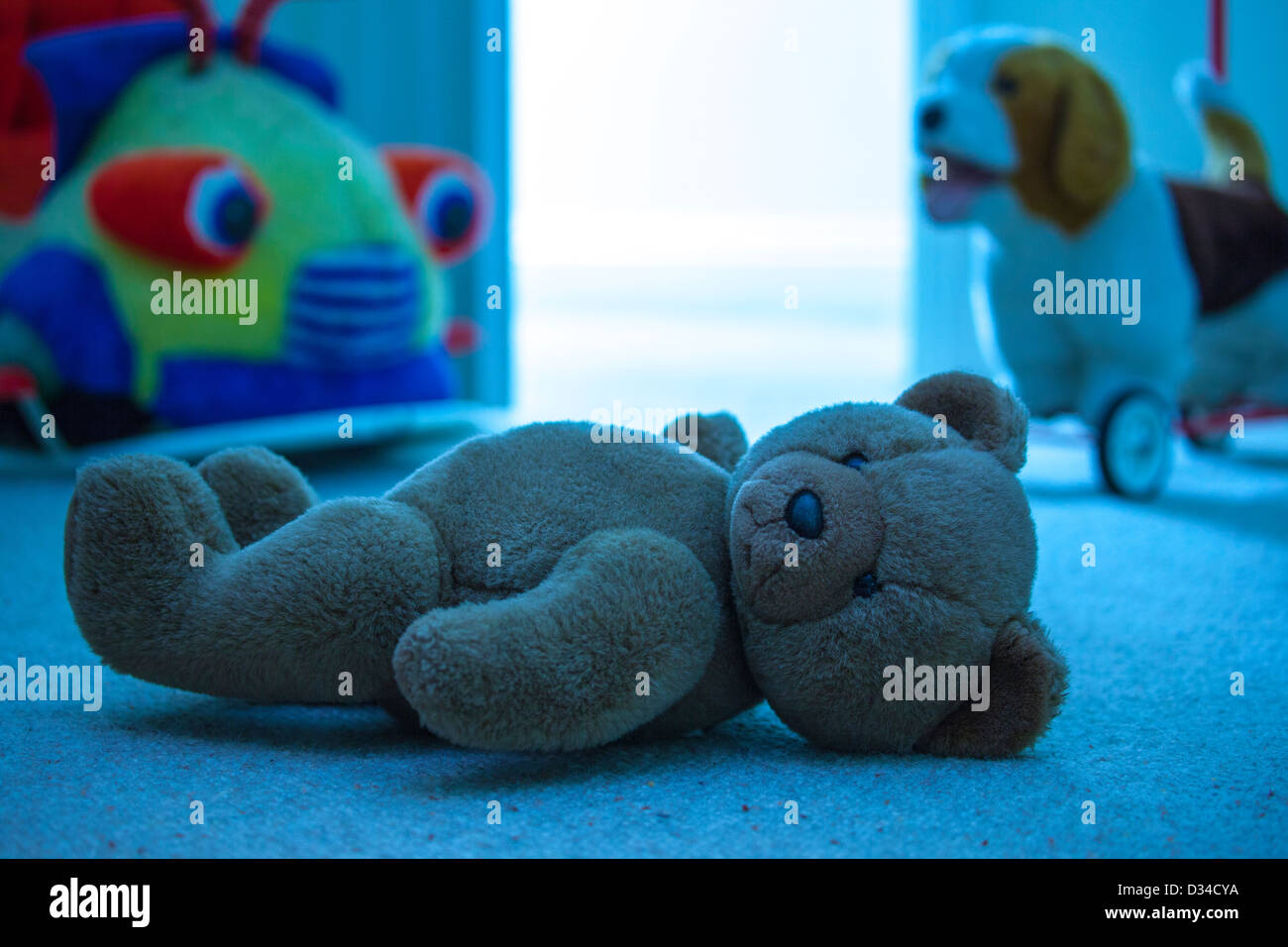 Brown teddy bear laying on a child's bedroom floor. Blue tone. - Stock Image