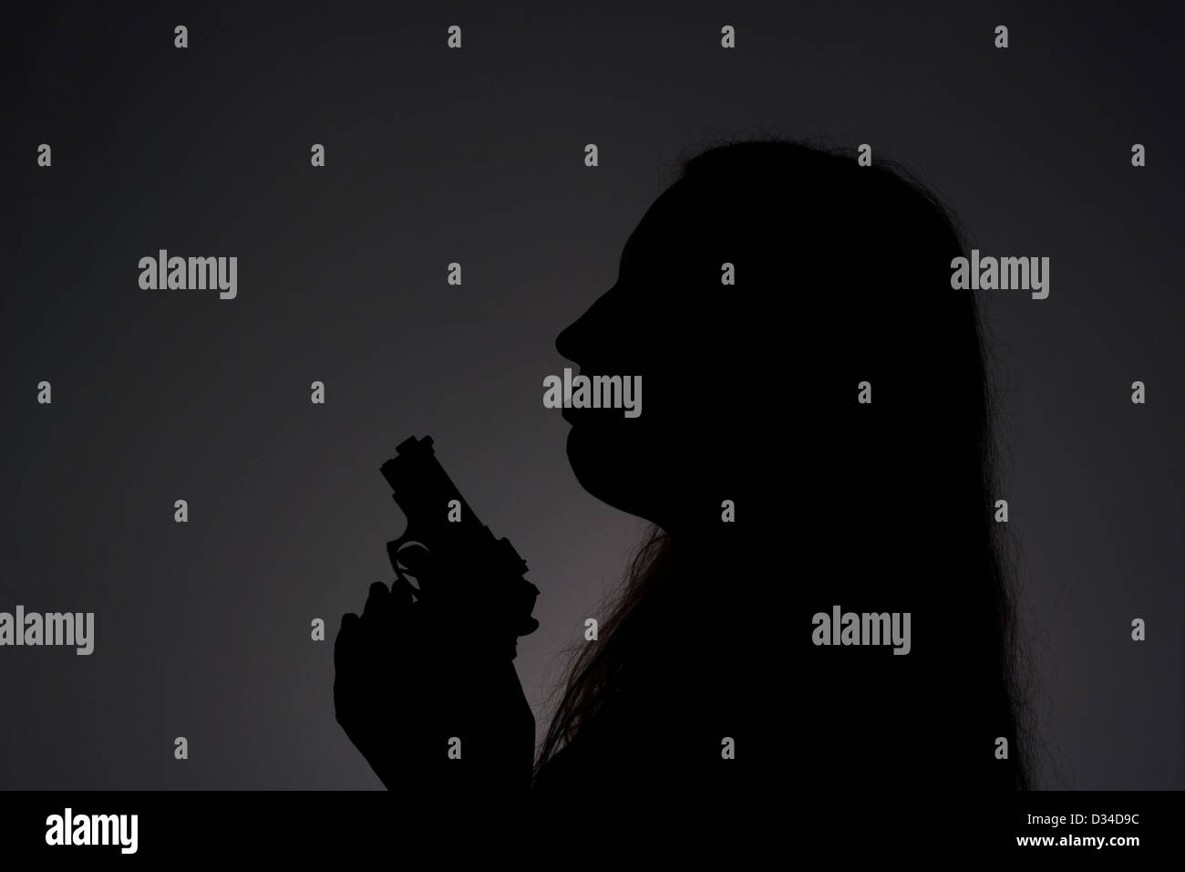Woman with gun in the darkness - Stock Image