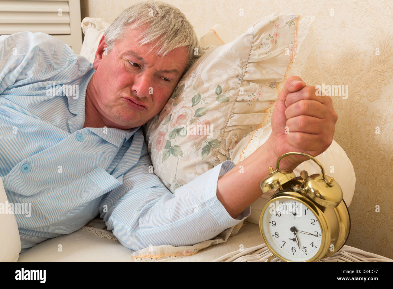 Bad tempered grumpy old man in bed - Stock Image