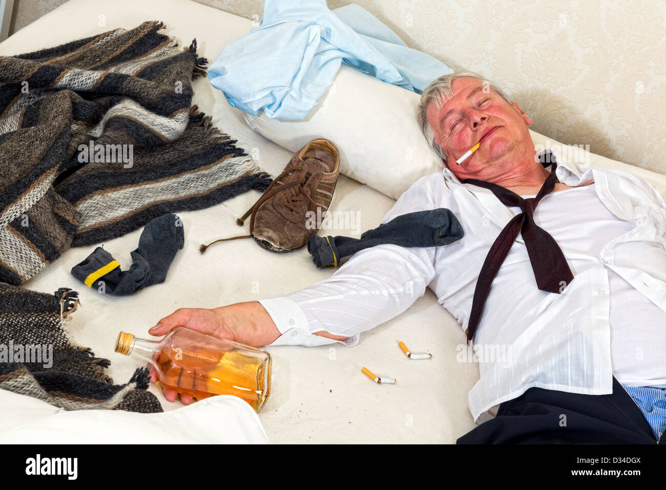 Drunken alcoholic sleeping in a messy bed - Stock Image
