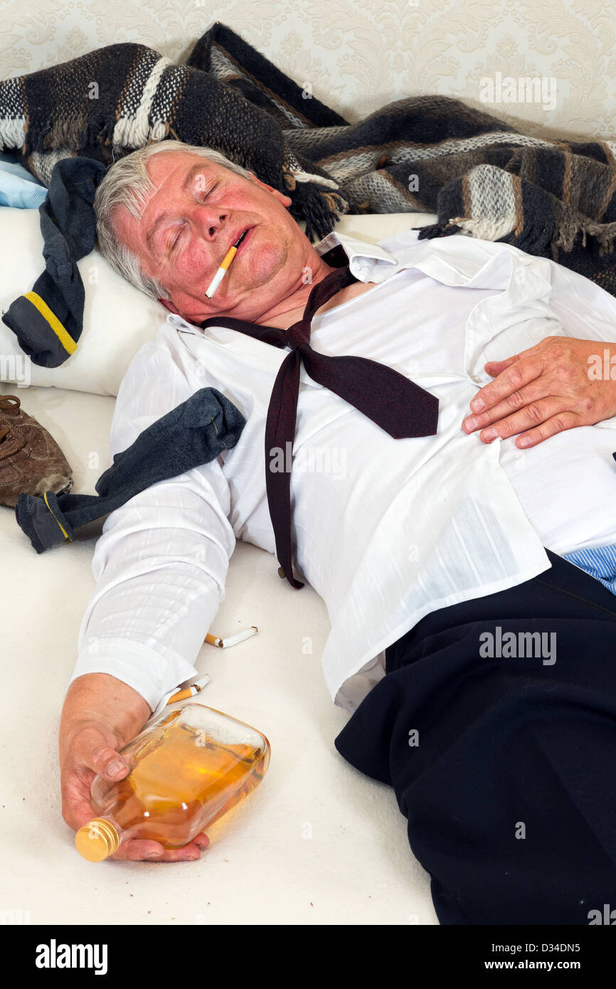 Drunk man lying in a messy bed - Stock Image