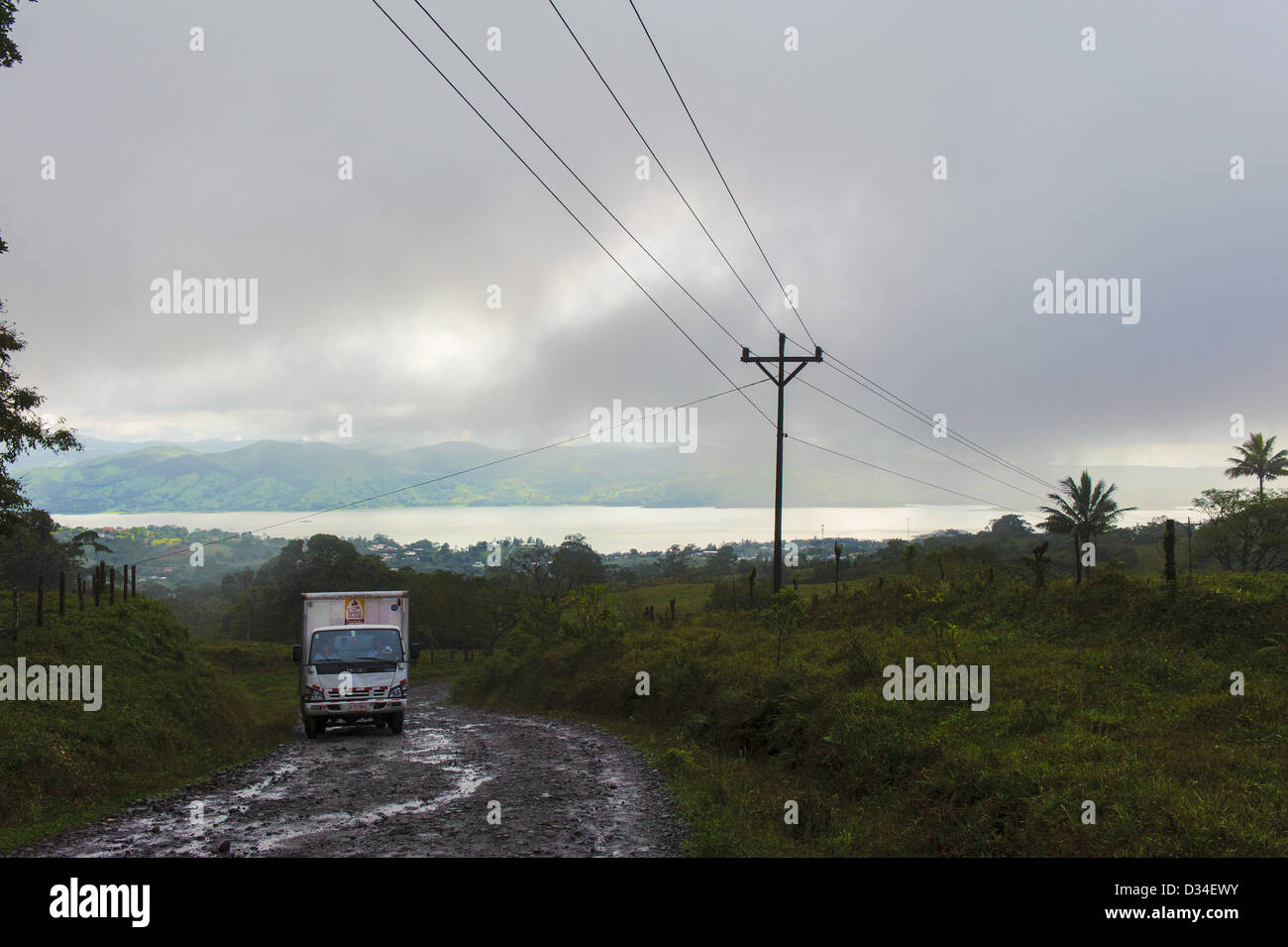 Passing truck on a wet dirt road leading to Lake Arenal near the village Nuevo Arenal . Costa Rica - Stock Image
