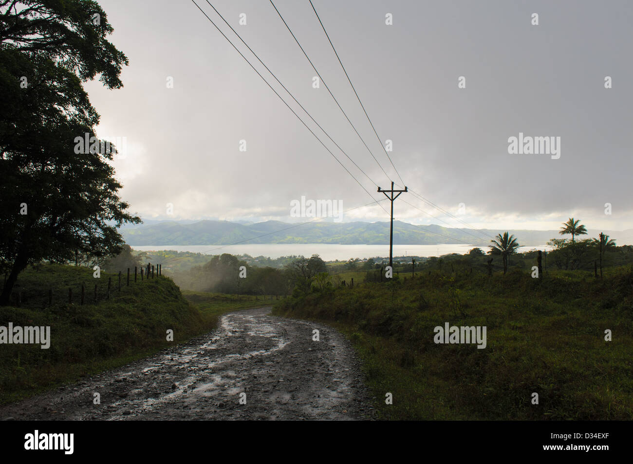 A wet dirt road leading to Lake Arenal. near the village Nuevo Arenal Costa Rica - Stock Image