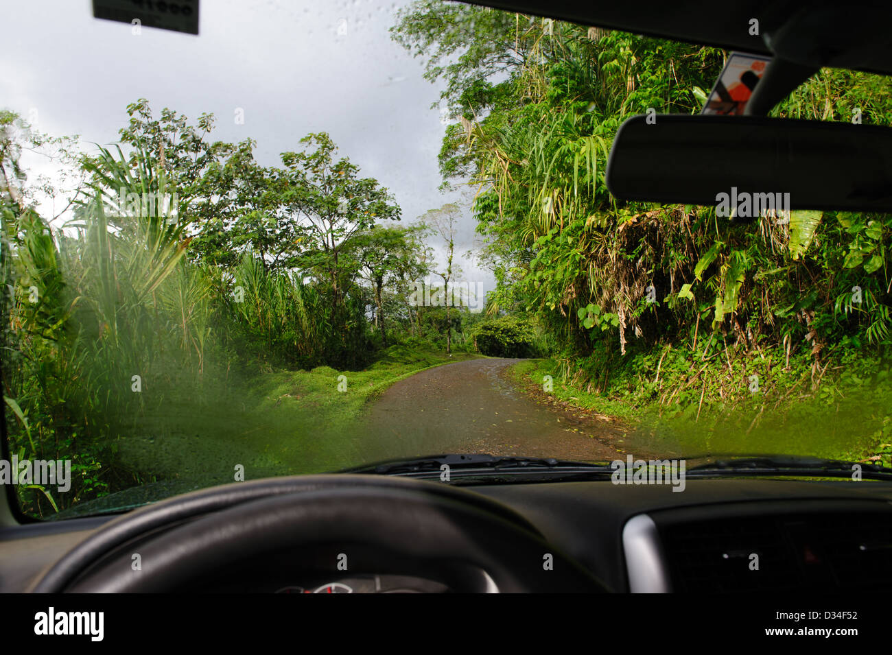 View through the damp windscreen of a car on a dirt road in ' Volcan Arenal National Park'. Costa Rica. - Stock Image