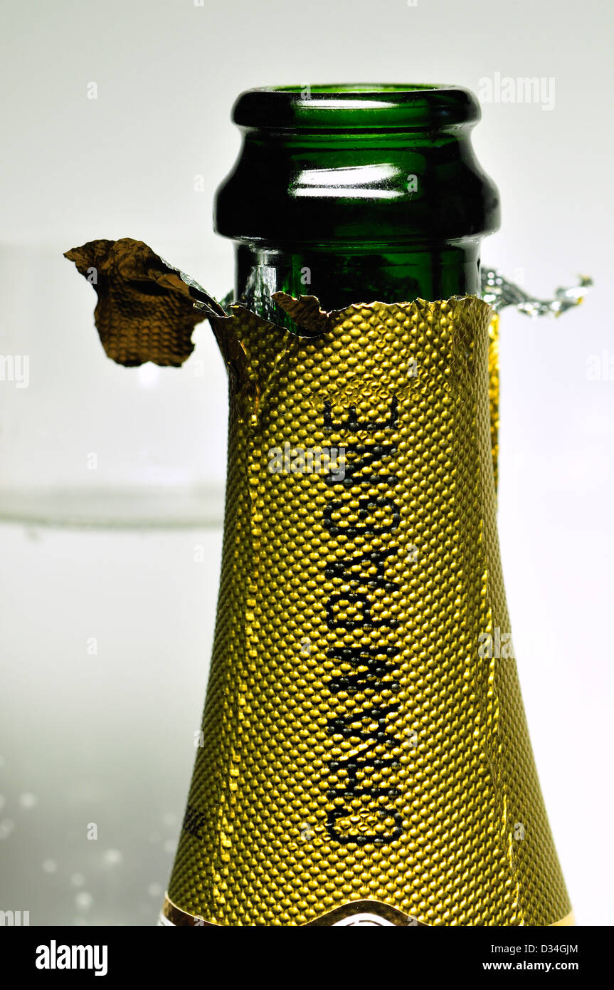 Open champagne bottle with twisted foil and glass - Stock Image