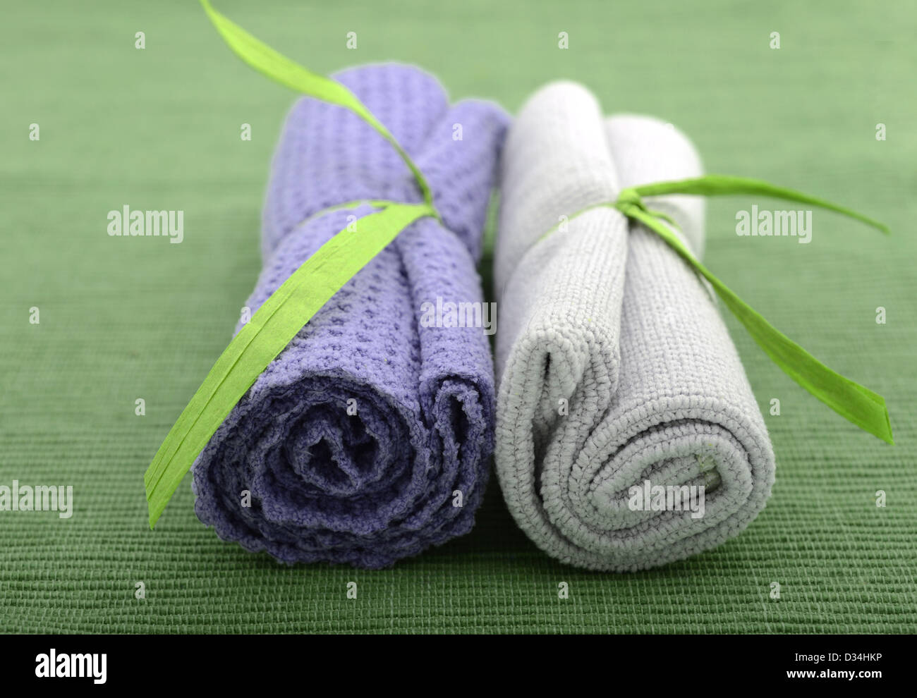 Purple and green wash cloths rolled up for bath at spa - Stock Image