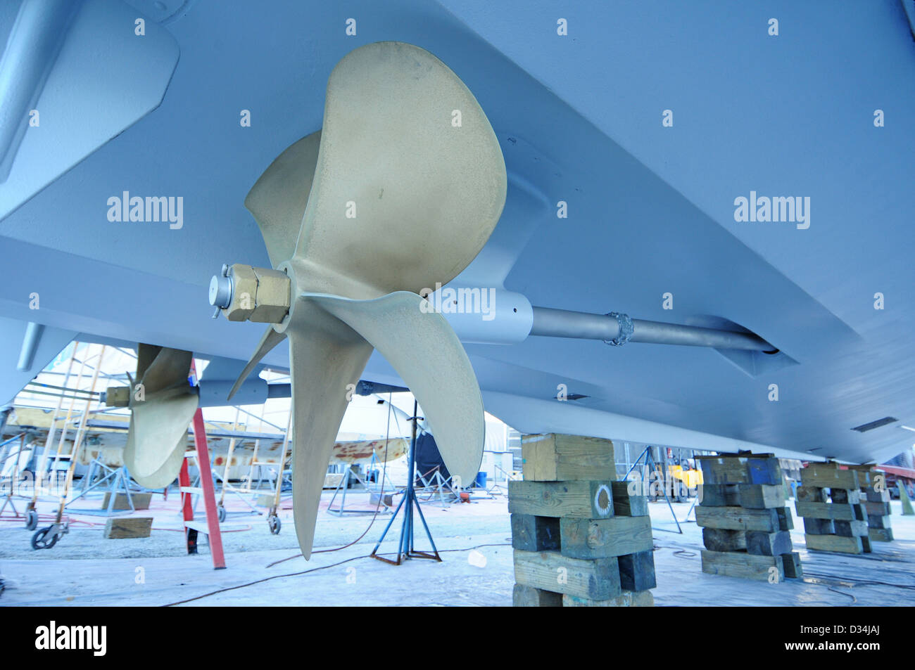 close up of boat propeller that is up on blocks in boat yard - Stock Image