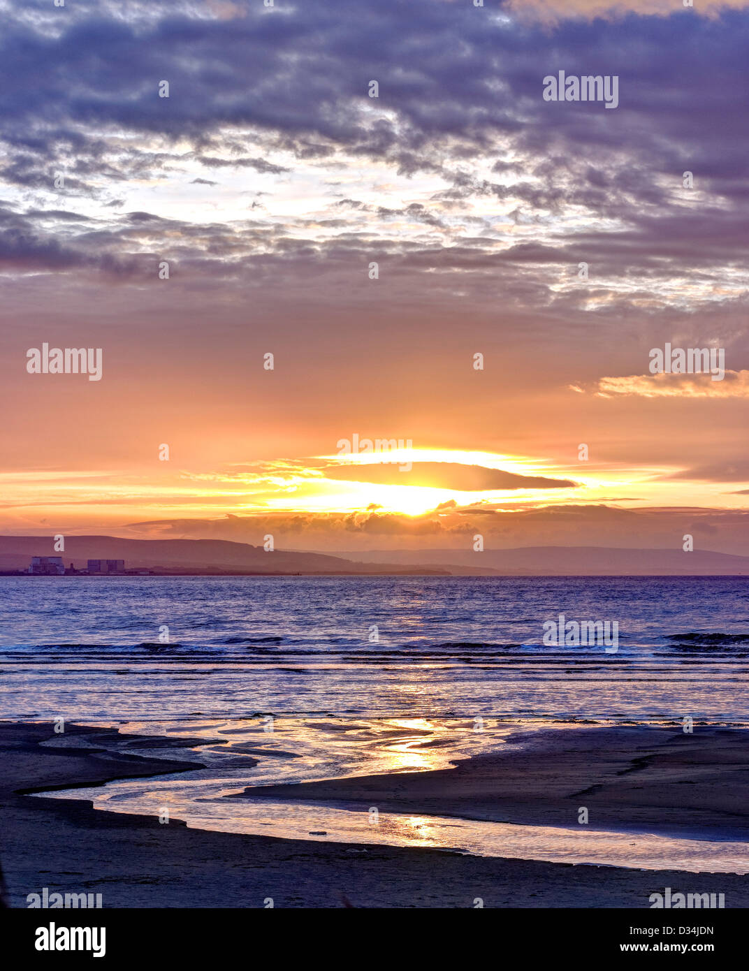 Outfall stream on Berrow beach near Burnham-on-Sea at sunset with Hinkley Point Nuclear Power Station, Somerset, Stock Photo
