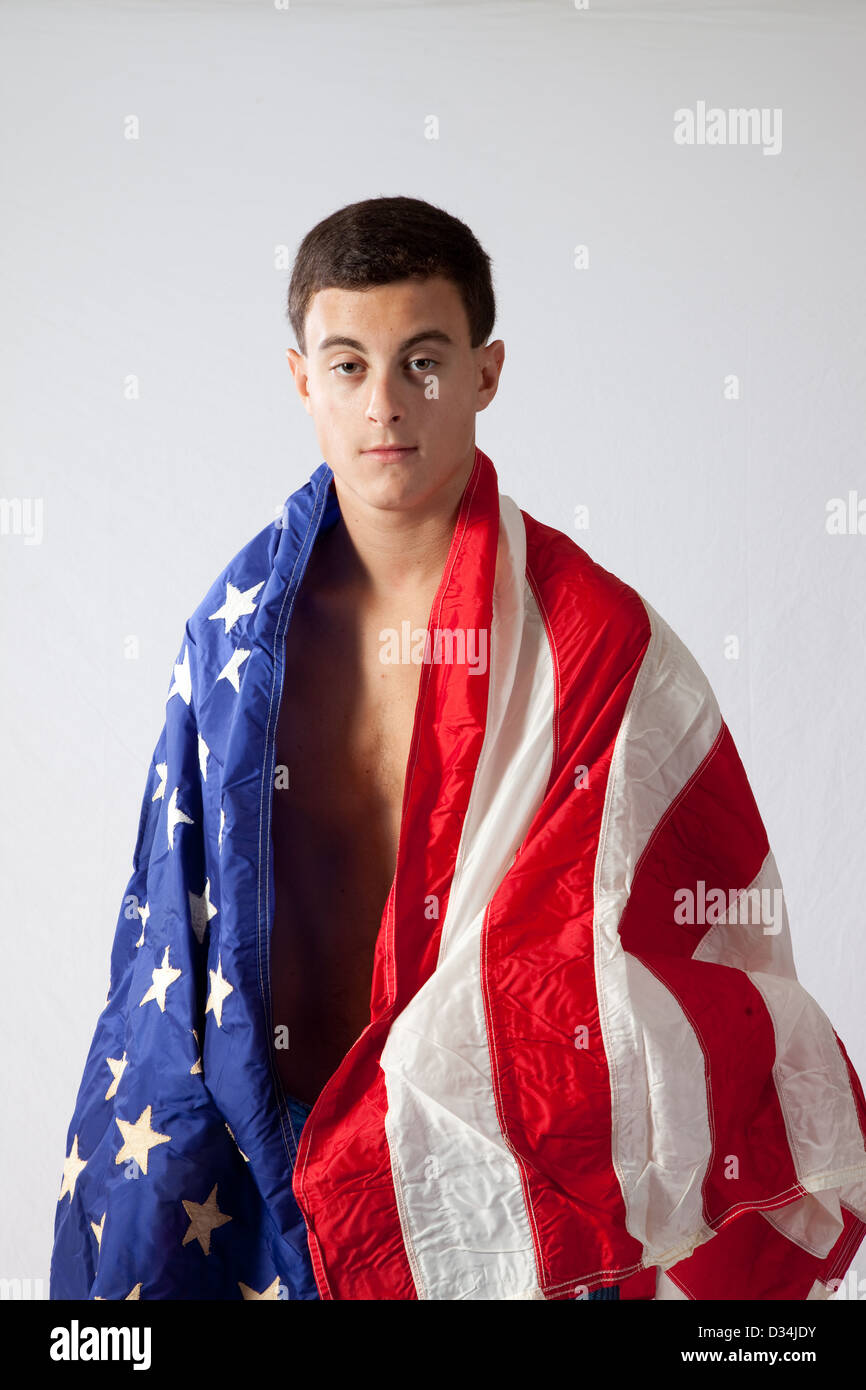 Young man without shirt, with his torso and shoulders wrapped in an American Flag and looking at the camera seriously - Stock Image