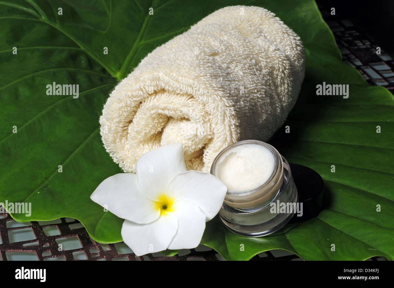 Moisturizer and a washcloth with a flower at a spa - Stock Image