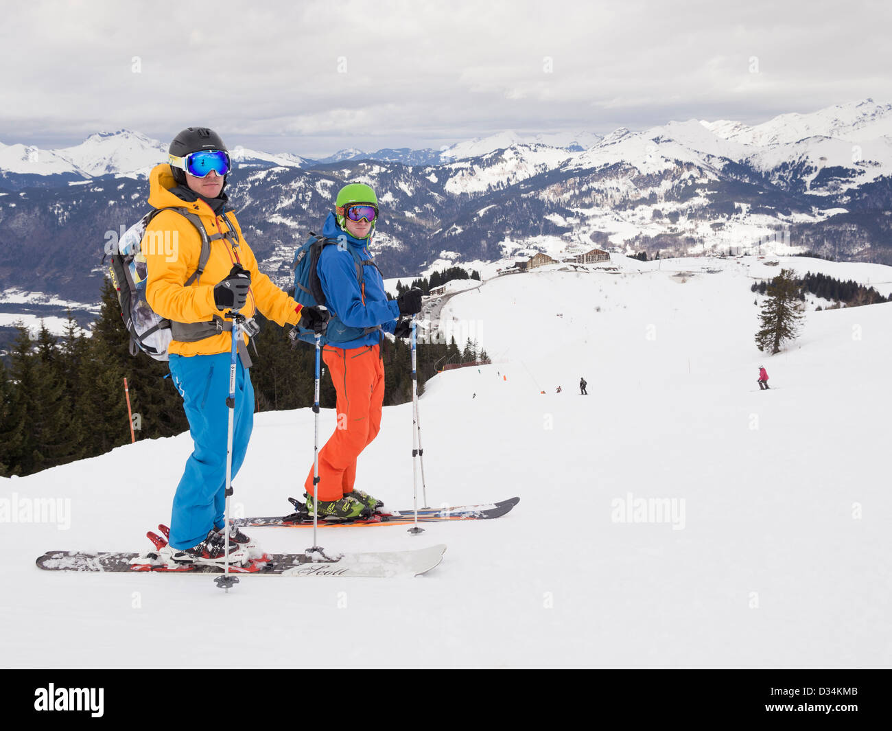Two male skiers skiing in flat light on red run Marmotte in Le Grand Massif ski area of French Alps above Samoëns - Stock Image