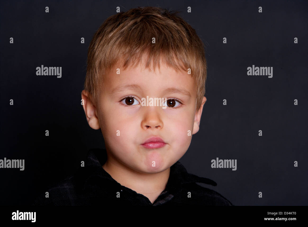4 Year old boy looking at apprehensive and nervously camera with a black background behind - Stock Image