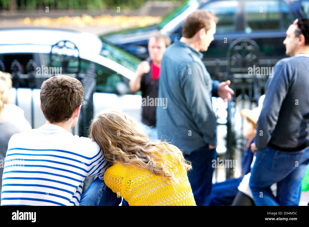 A young couple, a blonde girl and boy show affection whilst sitting. Stock Photo
