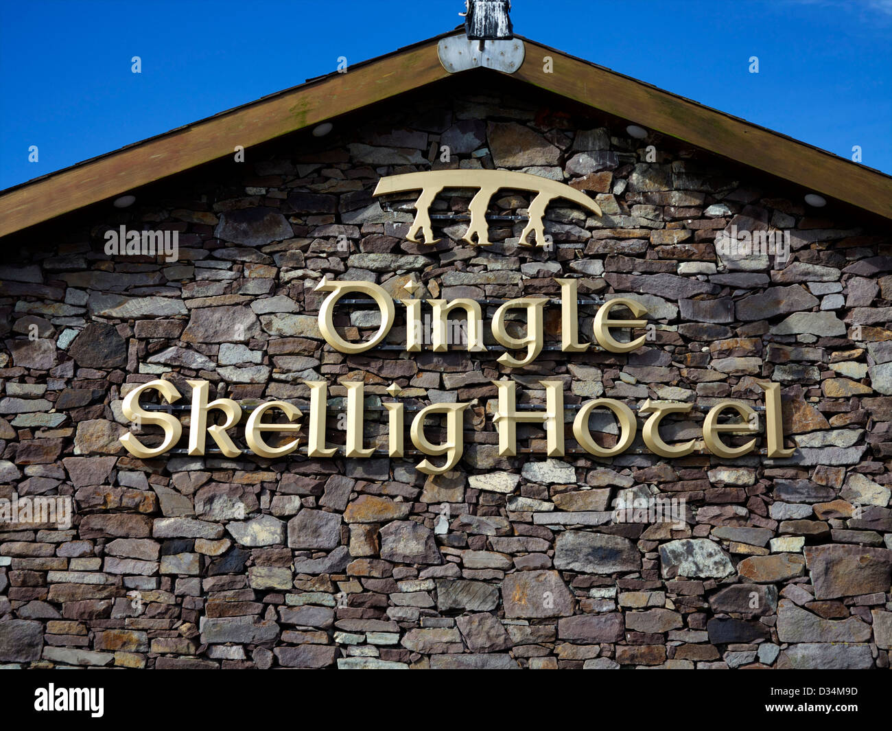 The name 'Dingle Skellig Hotel' in gold letters on granite in Dingle, county Kerry, Ireland with three men - Stock Image