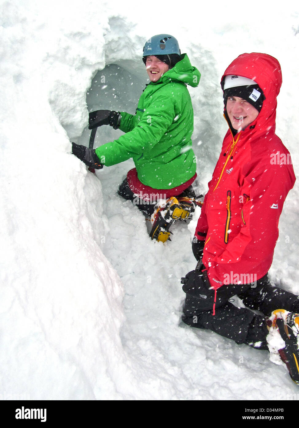 Two young men dig a snow hole in the Scottish highlands - Stock Image