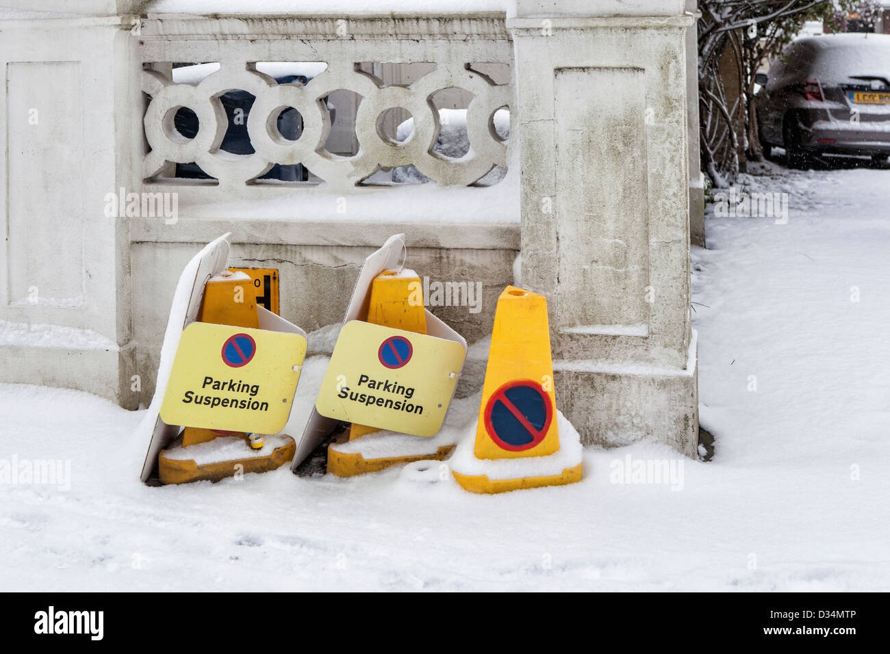 Parking suspension signs and no entry bollards in the snow in Winter - Richmond upon Thames, Surrey - Stock Image