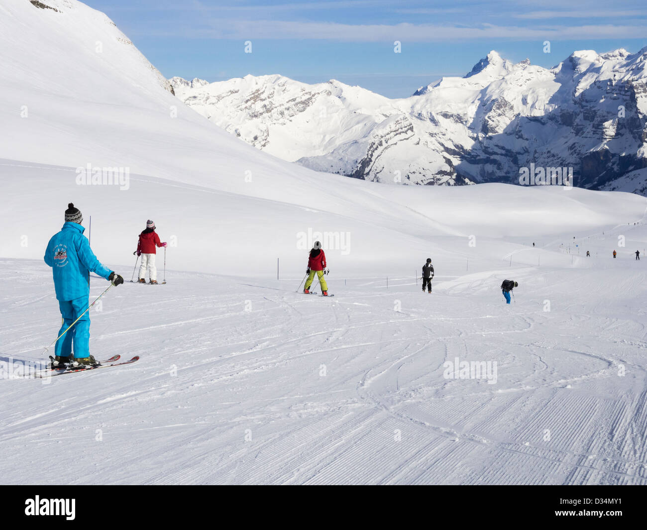 Skiers skiing down 14 km blue snow slope Les Cascades ski slope in Le Grand Massif ski area in French Alps. Flaine - Stock Image