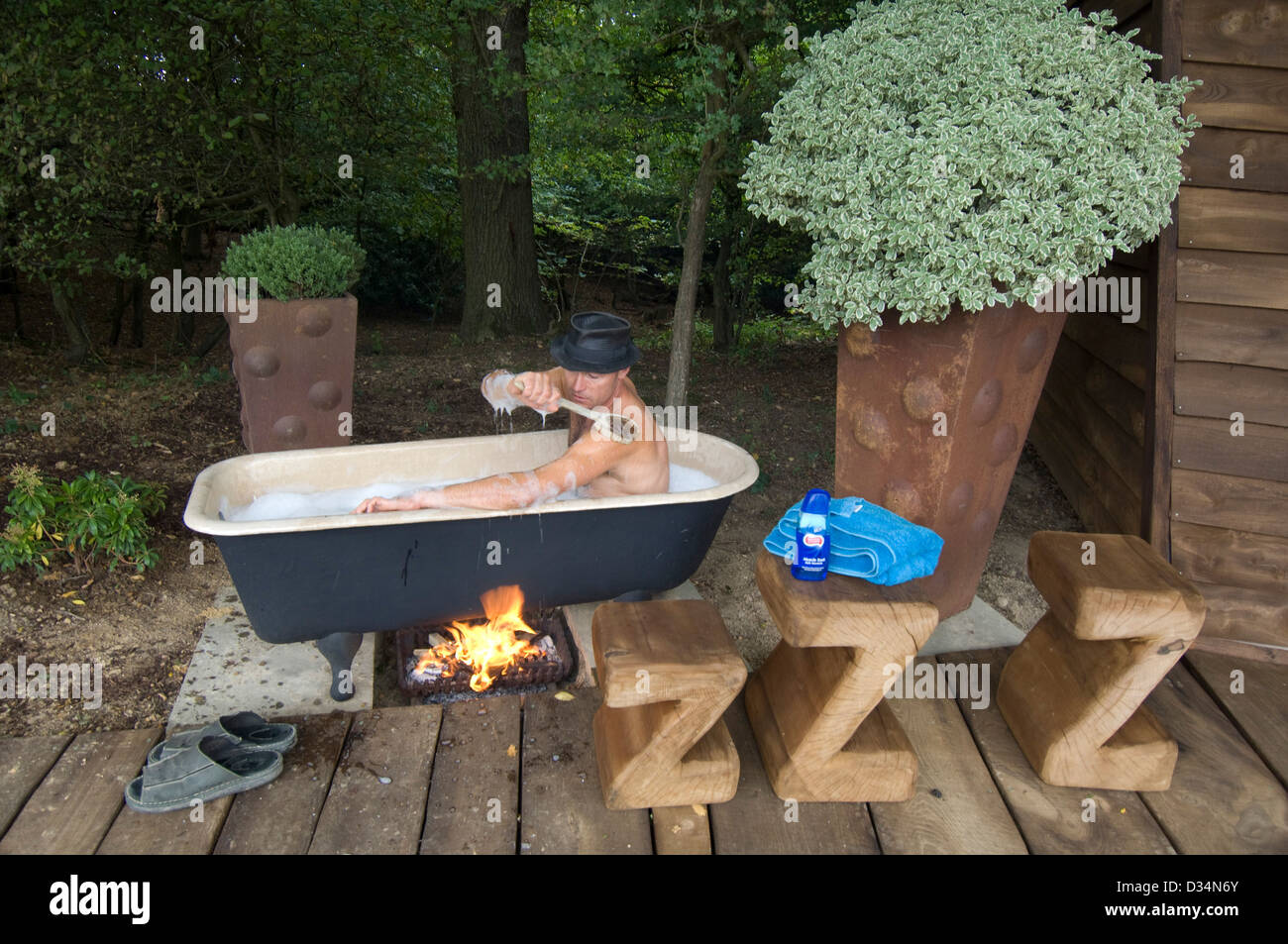 Man in outdoor bath heated by log fire Stock Photo ...