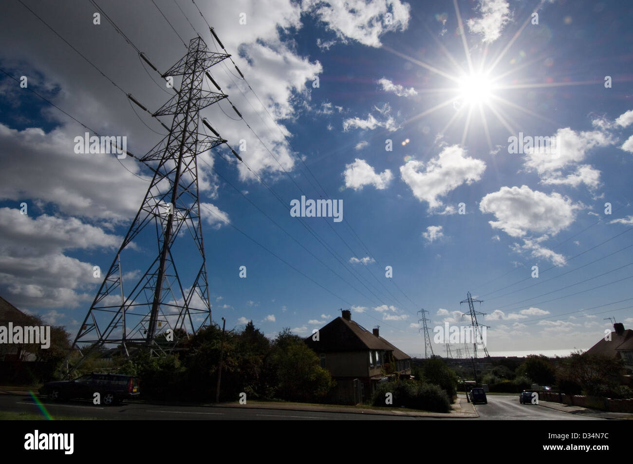 Pylons march across a housing estate - Stock Image
