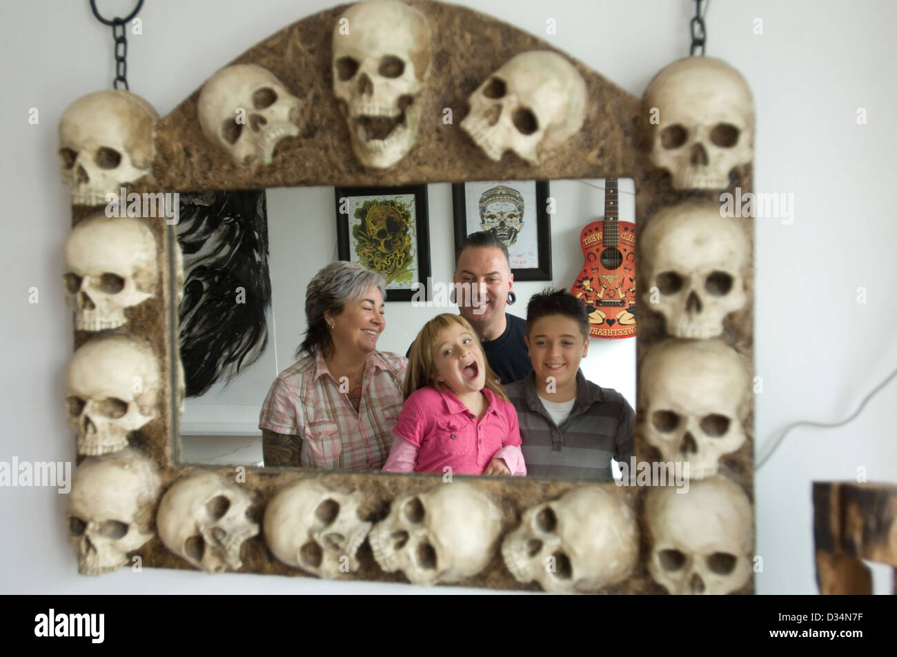 Young family reflected in a mirror with a frame of skulls - Stock Image