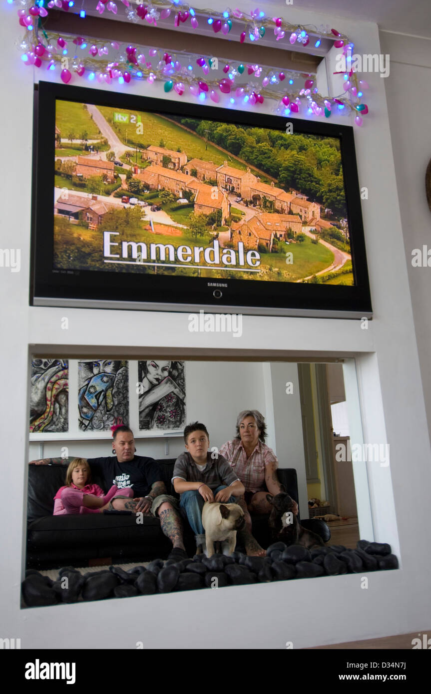 A family with tattooed dad watch their giant telly from a sofa as Emerdale begins - Stock Image