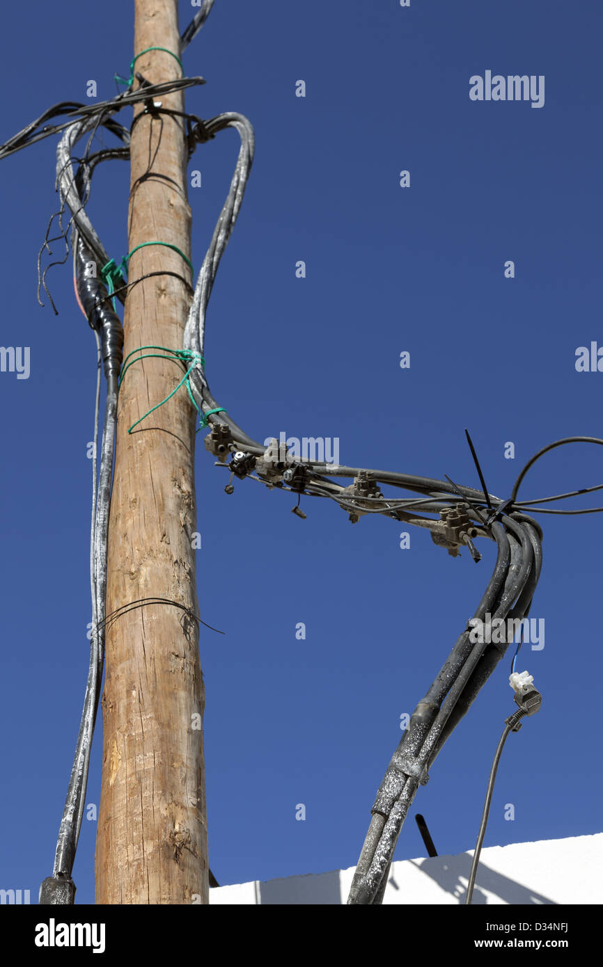 Dangerous twisted and exposed jumble of electrical cables, junctions and wires hanging from wooden pole - Stock Image