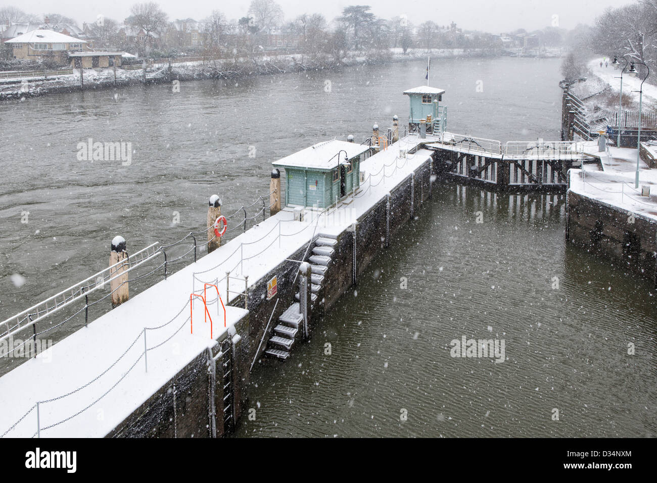 Richmond Lock and weir controls water levels of tidal river - Snow covered lock in Winter - River Thames, Richmond Stock Photo