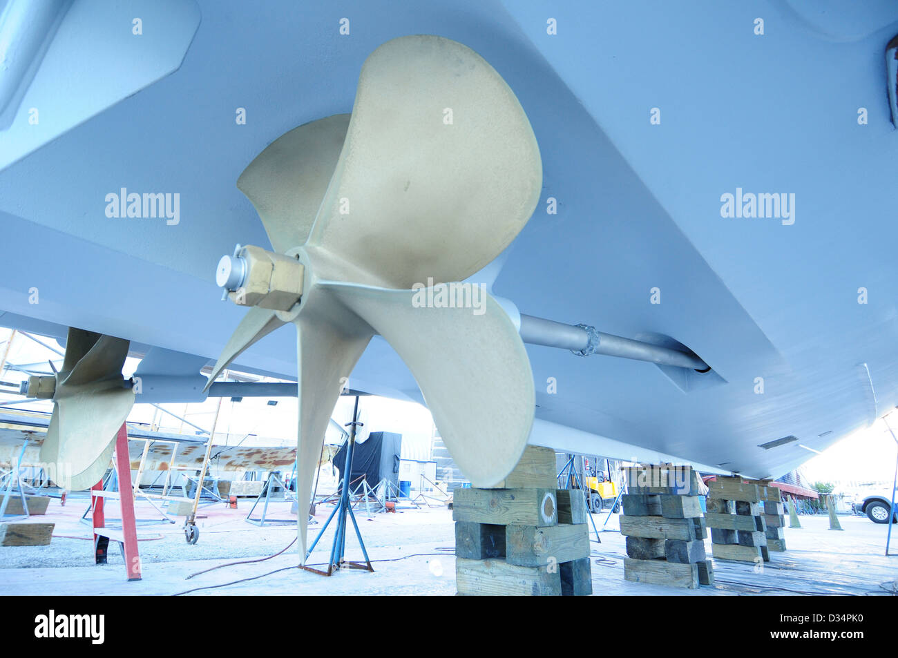 fixing boat propeller that is up on wood blocks - Stock Image