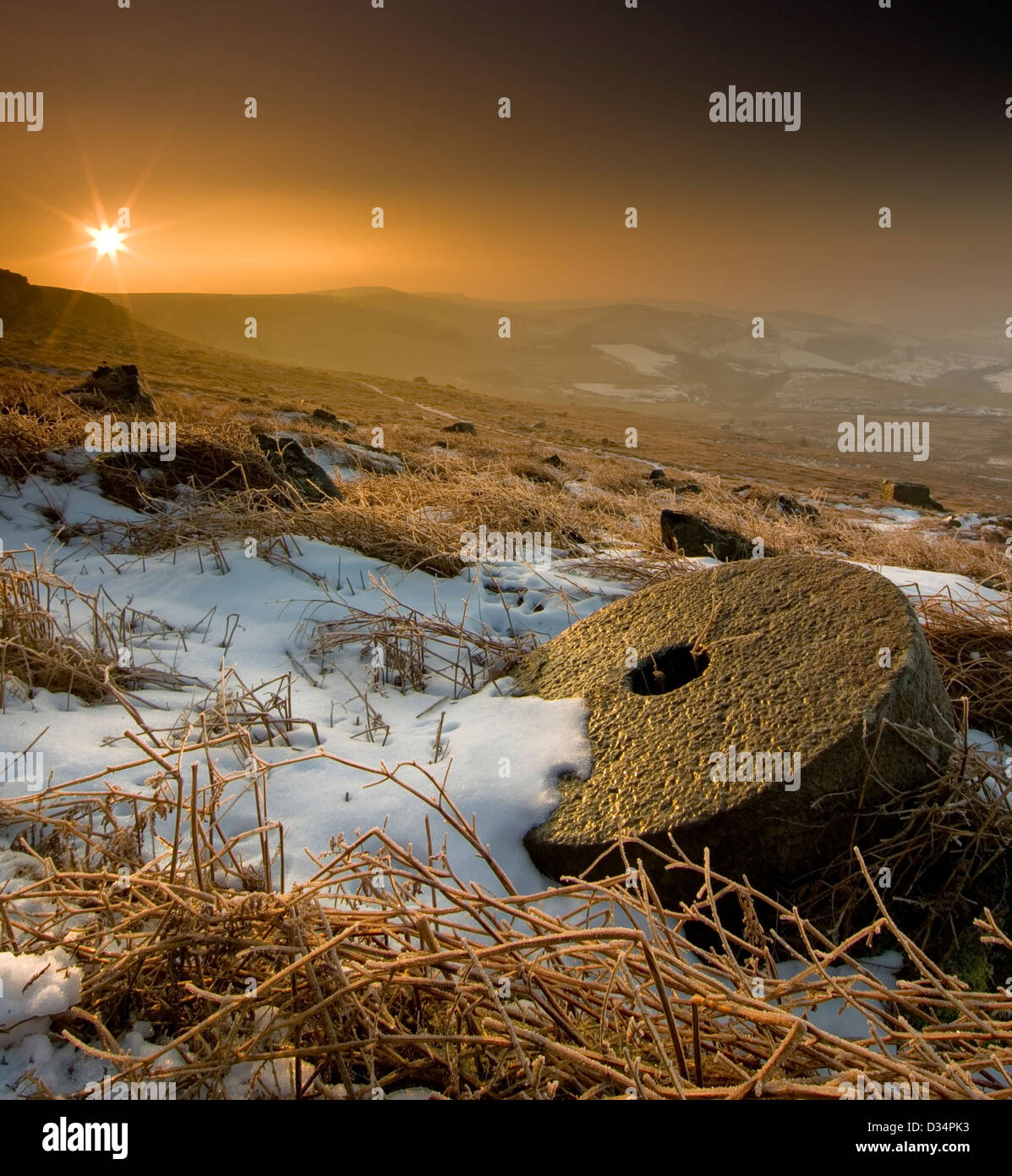Sunrise on Stanage Moor on a cold snowy morning with Millstone in foreground. - Stock Image