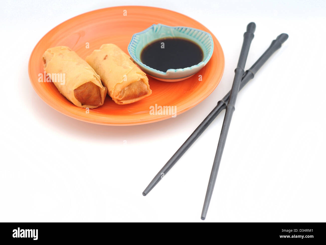 Two spring rolls or egg rolls with chopsticks - Stock Image