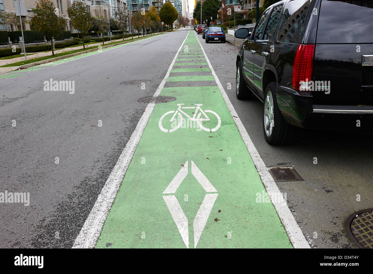cycle lane painted on road beside onstreet parking Vancouver BC Canada - Stock Image