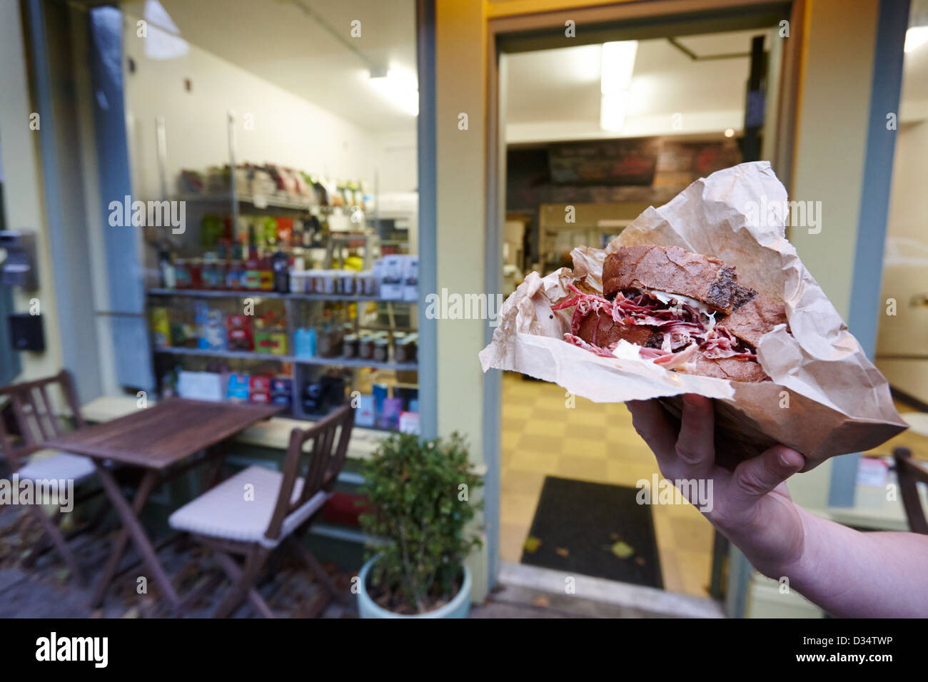 man holding hot reuben sandwich outside small deli in west end Vancouver BC Canada - Stock Image