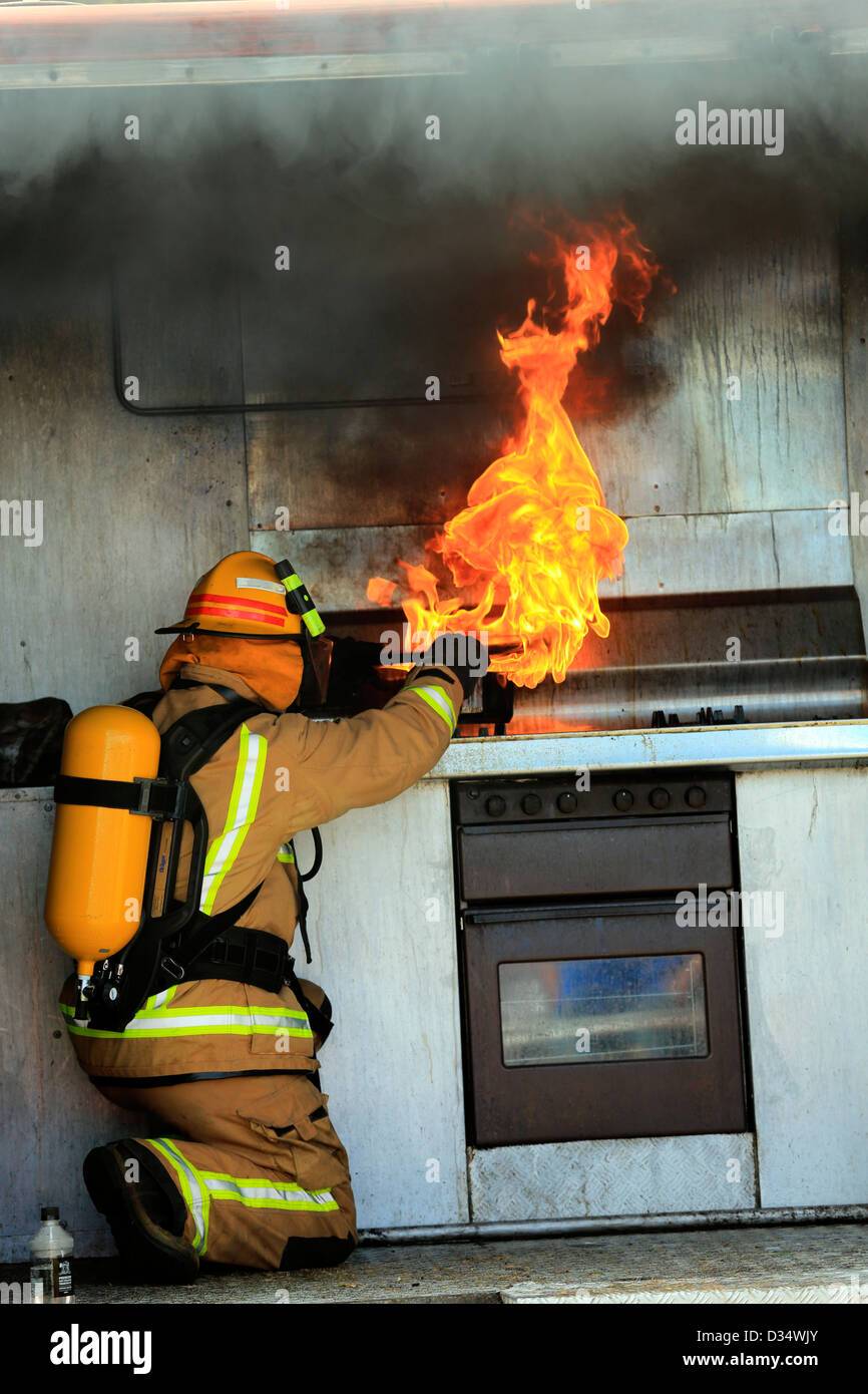 New Zealand Fire Service demonstration with fireman showing how to control a kitchen fire - Stock Image