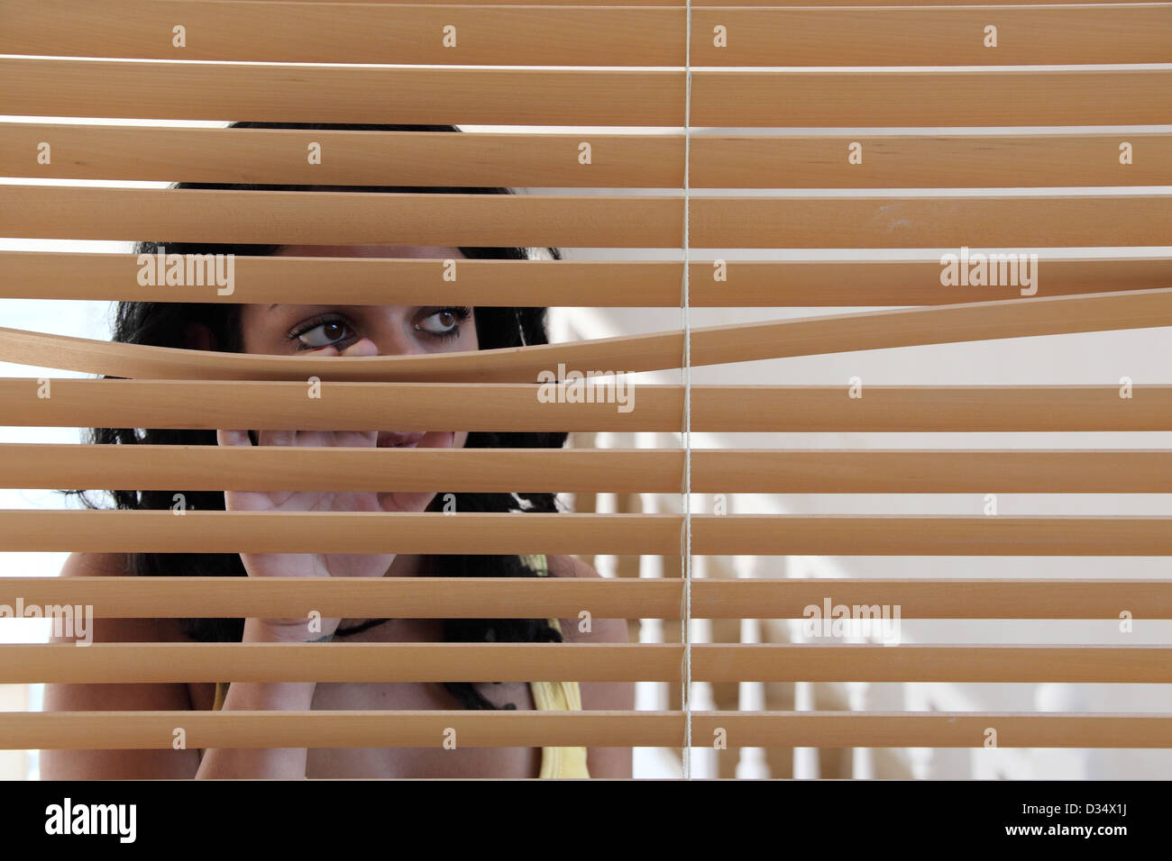 Young dark haired female behind a window blind, looking out of the window. - Stock Image