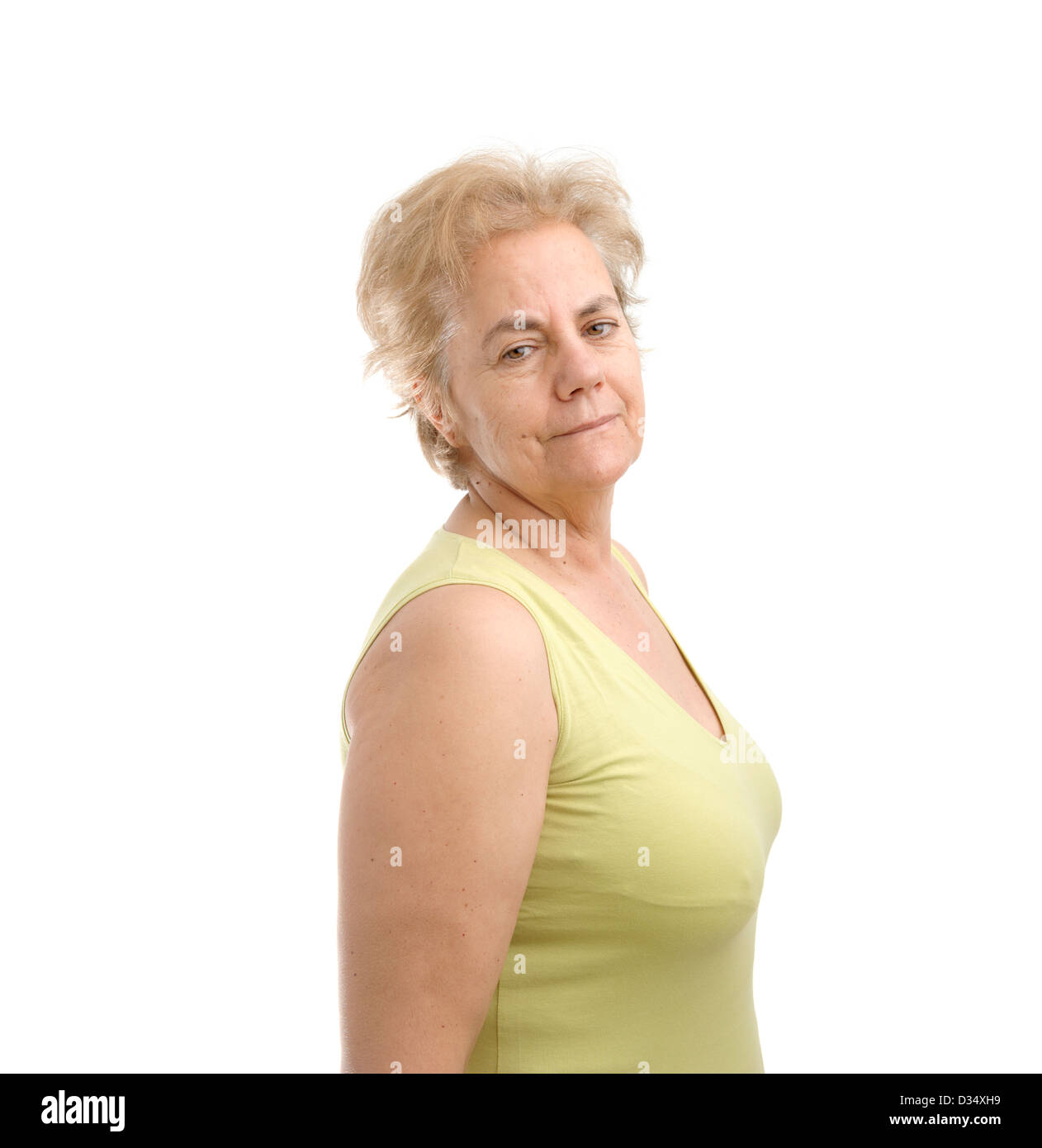 Confident middle aged woman wearing a green sleeveless shirt and looking over her right shoulder isolated on white - Stock Image