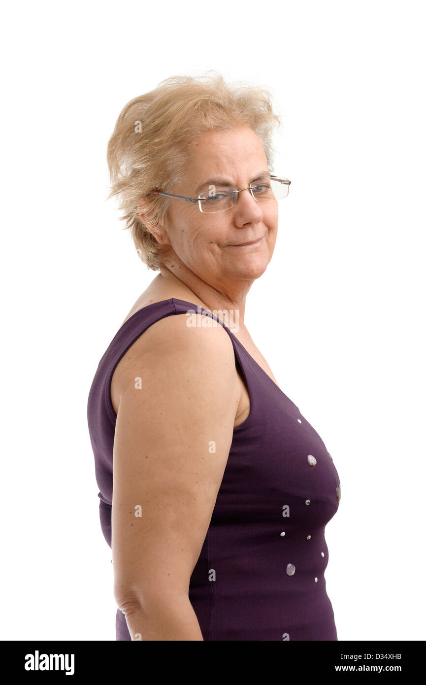 Confident middle aged woman wearing a purple sleeveless shirt and looking over her right shoulder isolated on white - Stock Image