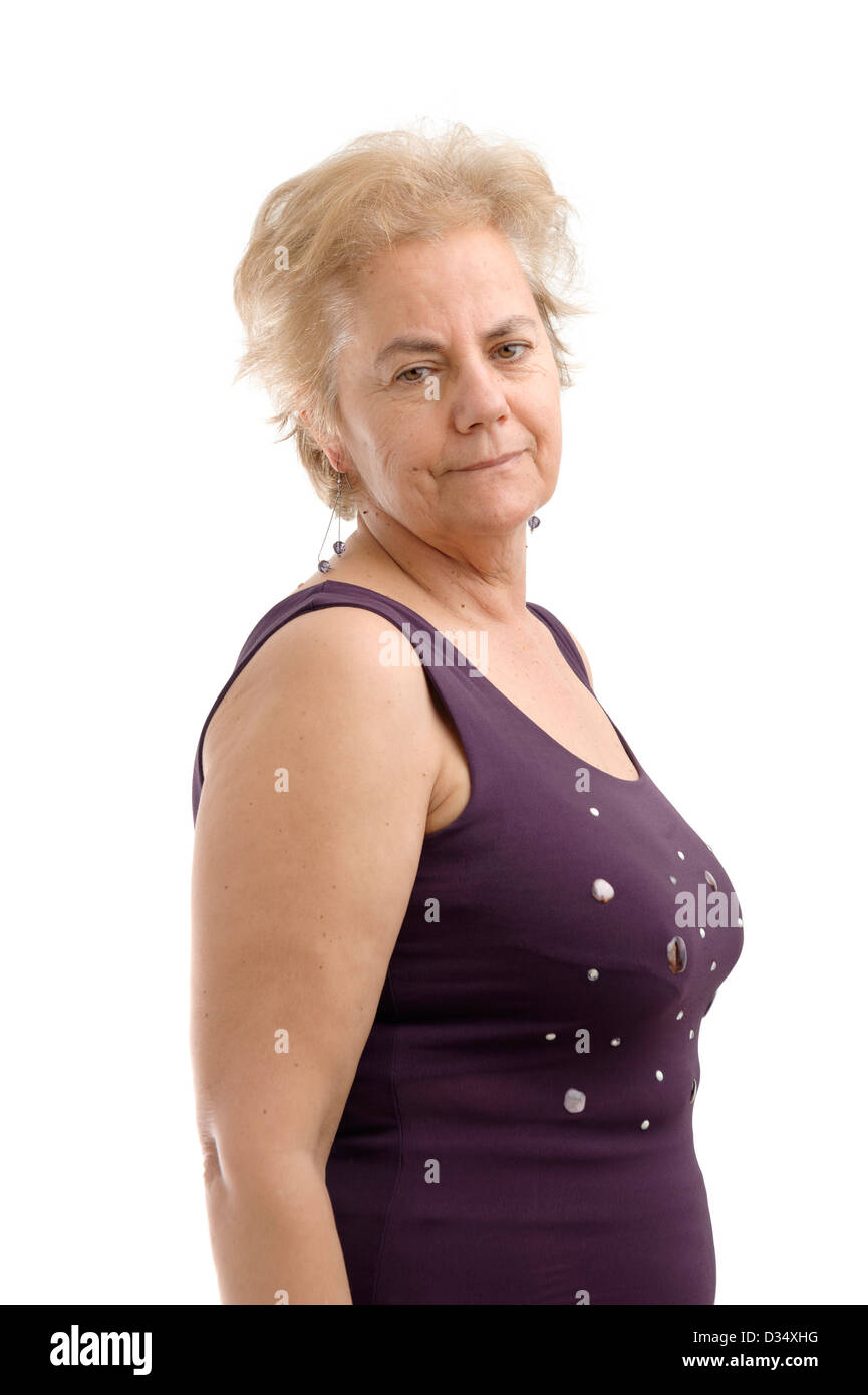 Confident mature woman wearing a purple sleeveless shirt and looking over her right shoulder isolated on white background - Stock Image